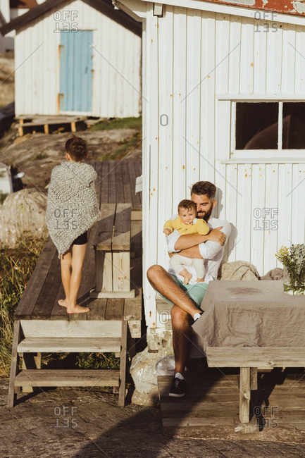 Smiling father embracing baby girl while boy covered in blanket walking by cabin
