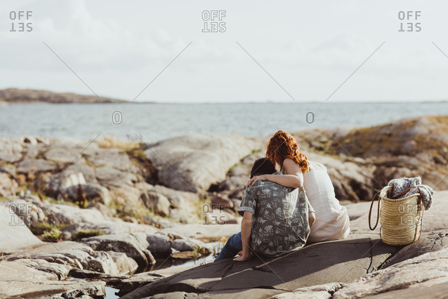 Rear view of mother and son bonding while sitting over rocky land during sunny day