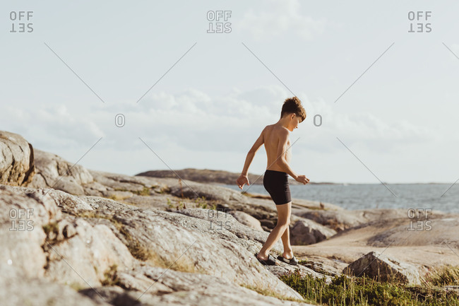 Shirtless boy walking on archipelago during weekend