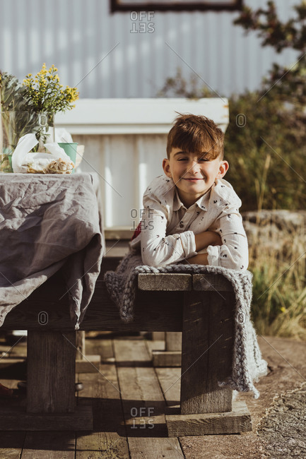 Portrait of smiling boy lying on front over wooden seat