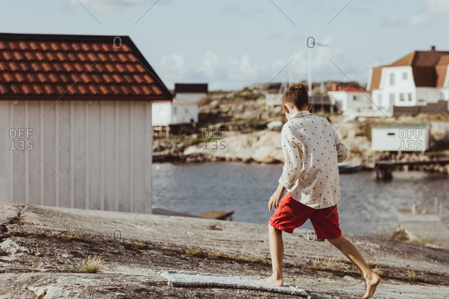 Boy walking over blanket on archipelago during sunny day