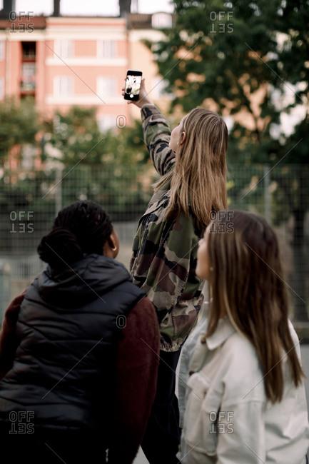 Teenage girl taking selfie with friends through smart phone in city