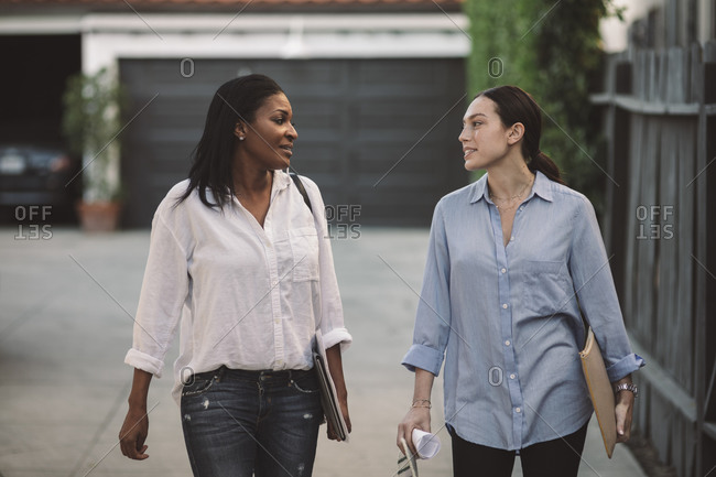 Female architects discussing while walking on footpath