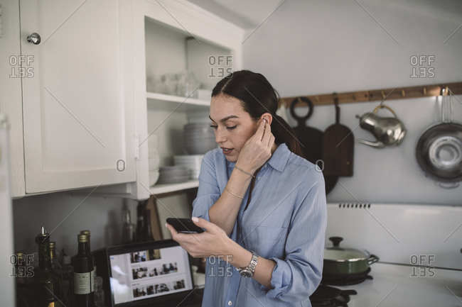 Female design professional wearing in-ear headphones at home office