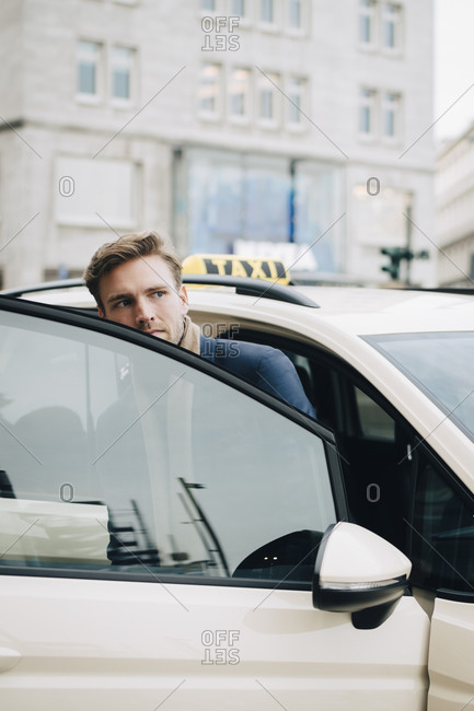 Businessman looking away while coming out of taxi during business trip in city