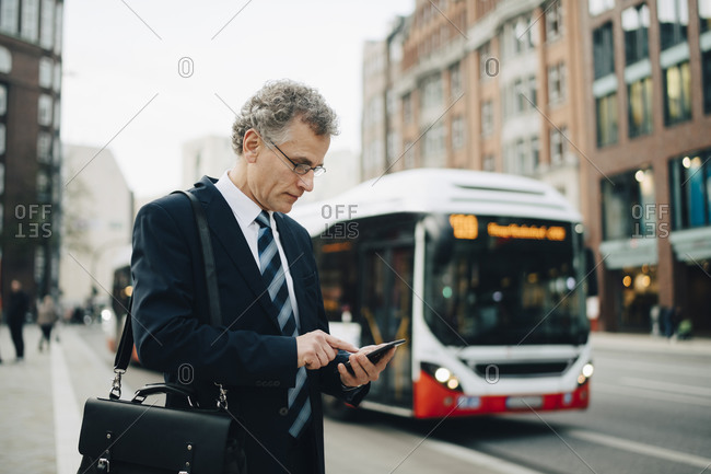 Mature businessman using smart phone while standing in city
