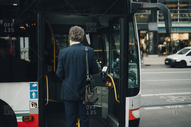 Rear view of male entrepreneur entering bus during business trip in city