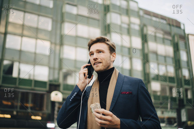 Confident businessman with wrap sandwich talking through smart phone while standing in city