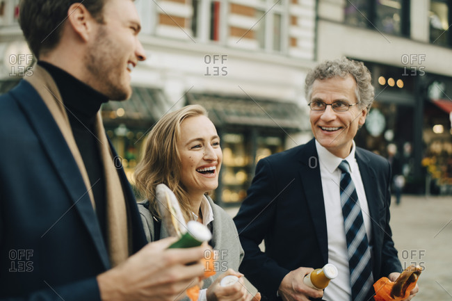 Smiling business colleagues discussing while holding food and drink in city
