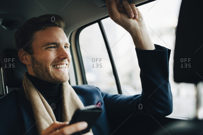 Smiling businessman with phone looking away while sitting in taxi