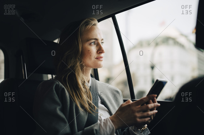 Contemplating female entrepreneur with smart phone looking through window while sitting in taxi
