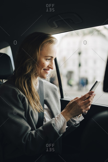 Smiling entrepreneur using smart phone while sitting in taxi