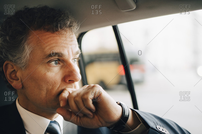 Contemplating entrepreneur looking through window while sitting in taxi