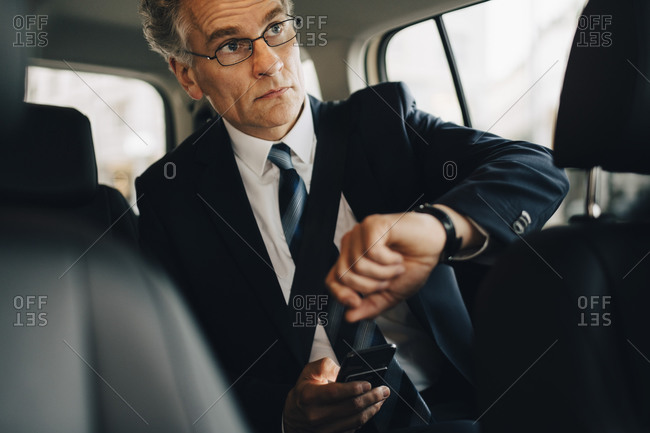 Businessman wearing wristwatch during business trip while sitting in taxi