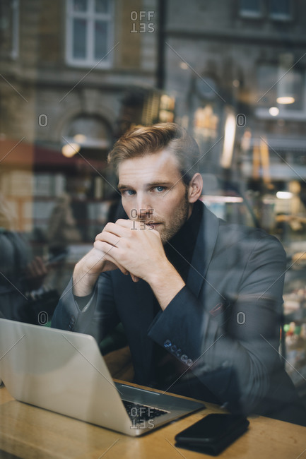 Portrait of businessman with laptop sitting in cafe seen through glass window