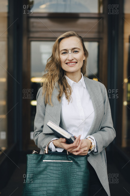 Portrait of smiling businesswoman with book and bag standing by store in city