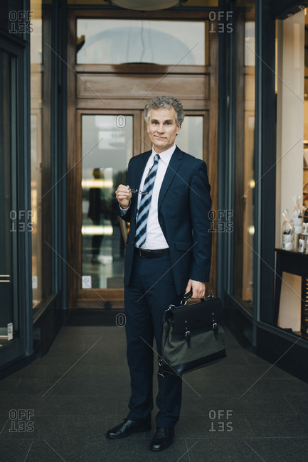 Portrait of businessman with bag standing by store in city