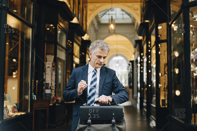 Mature businessman with bag looking at wristwatch while standing in city