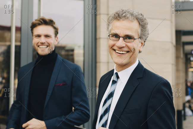 Portrait of happy male entrepreneur with colleague standing in city