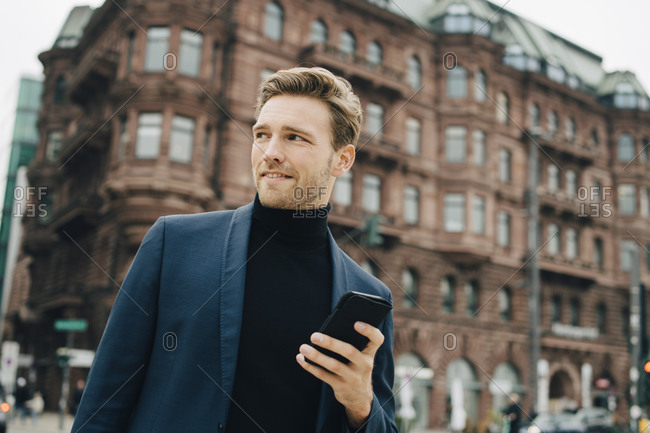 Confident businessman with smart phone looking away while standing against building in city