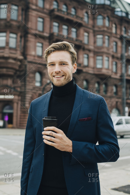 Portrait of businessman with disposable cup standing against building in city