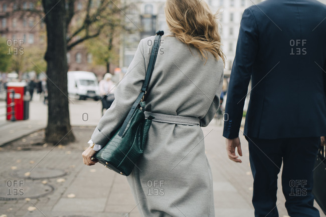 Rear view of businesswoman with handbag walking by colleague in city