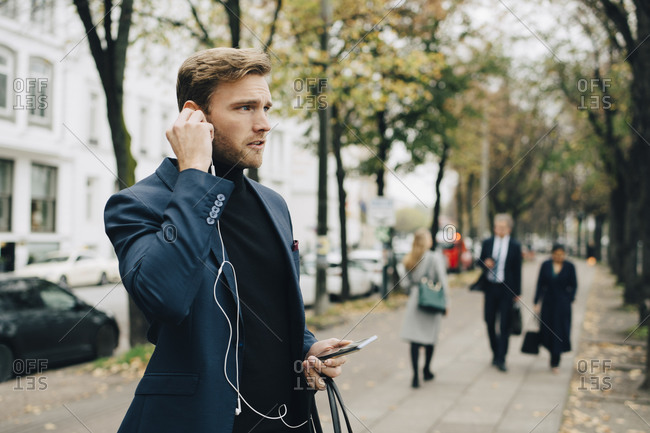 Businessman looking away while holding in-ear headphones in city