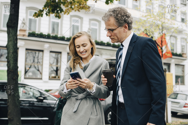 Smiling businesswoman showing smart phone to male coworker in city