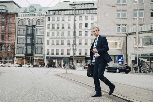 Mature entrepreneur using smart phone while crossing road in city