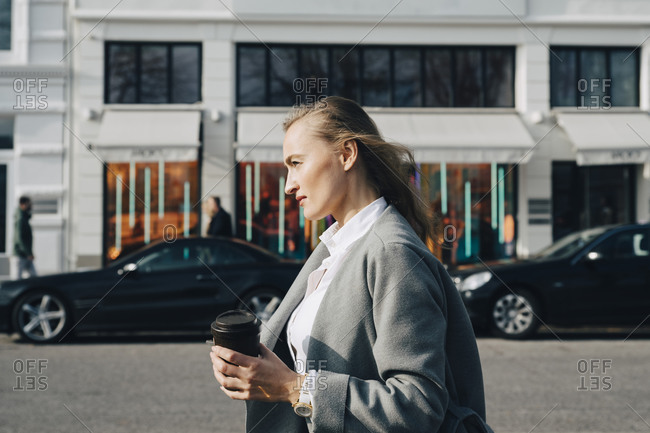 Side view of contemplating entrepreneur with disposable cup looking away while standing in city