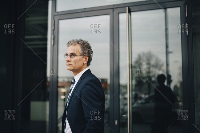 Side view of businessman wearing suit looking away while standing in city