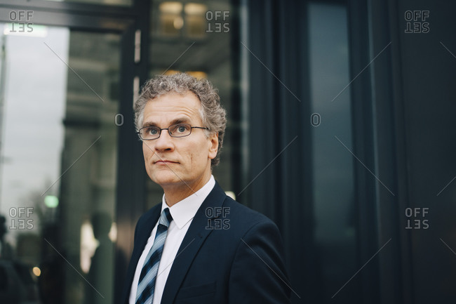 Male businessman wearing suit looking away while standing in city