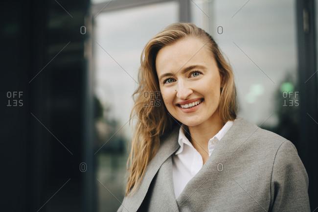 Portrait of smiling entrepreneur standing in city