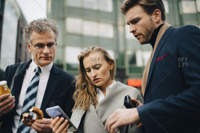 Low angle view of worried business people looking at mobile phone while standing in city
