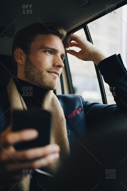 Confident businessman in suit looking through window while sitting in taxi