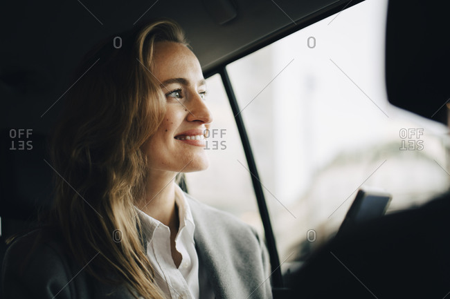 Confident smiling entrepreneur looking through window while sitting in taxi