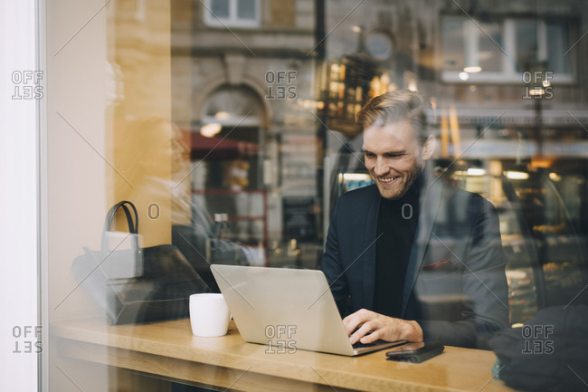 Smiling businessman using laptop in cafe seen through glass window