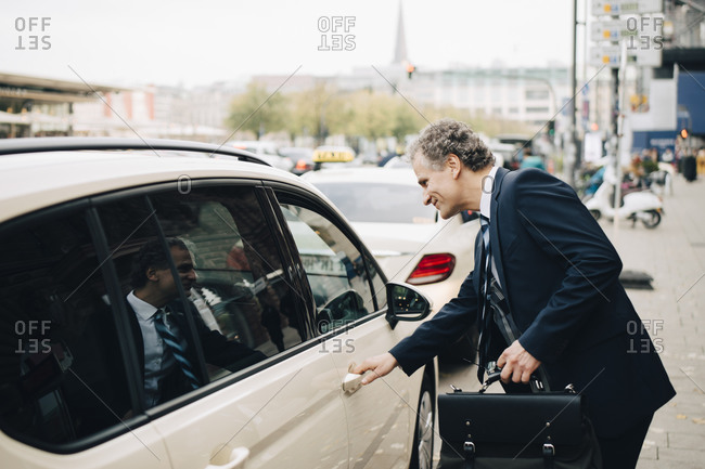 Side view of mature businessman holding taxi door in city