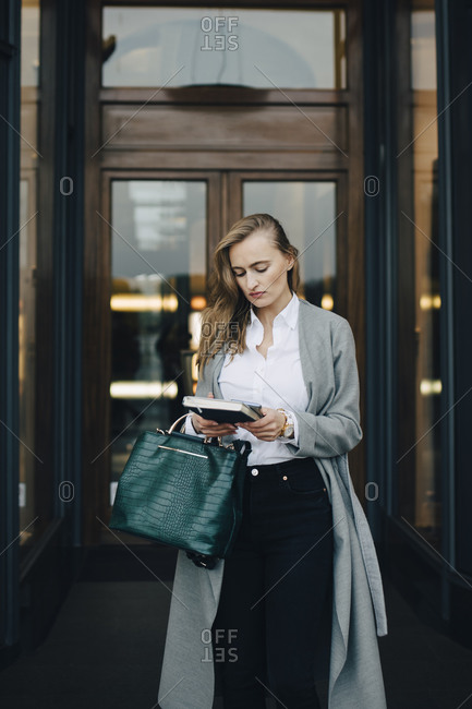 Businesswoman with book standing by store in city