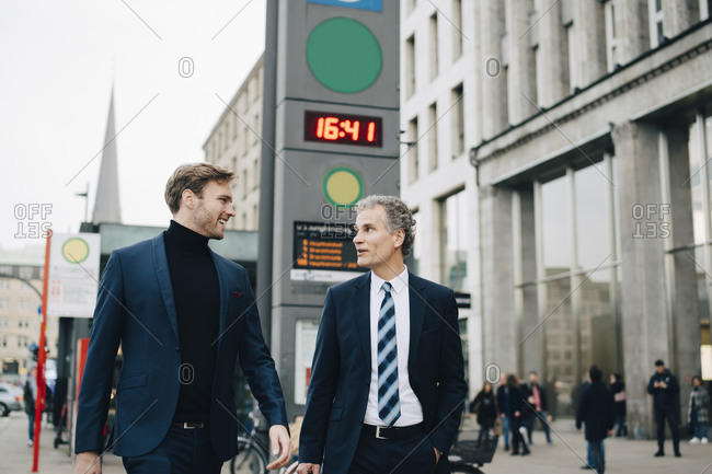 Businessman with male colleague walking in city