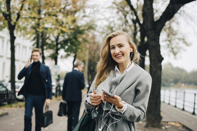 Smiling businesswoman with in-ear headphones and smart phone standing in city