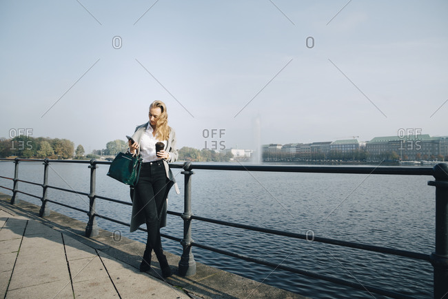 Full length of entrepreneur using mobile phone while standing against sea in city