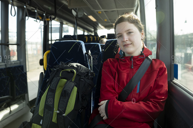 Portrait of teenage girl sitting with backpack in bus