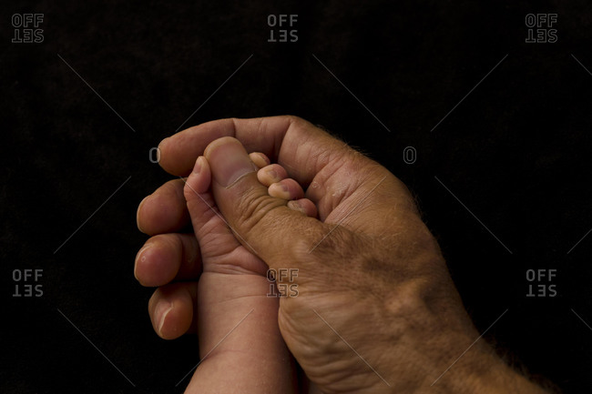 Father's hand holding baby's hand