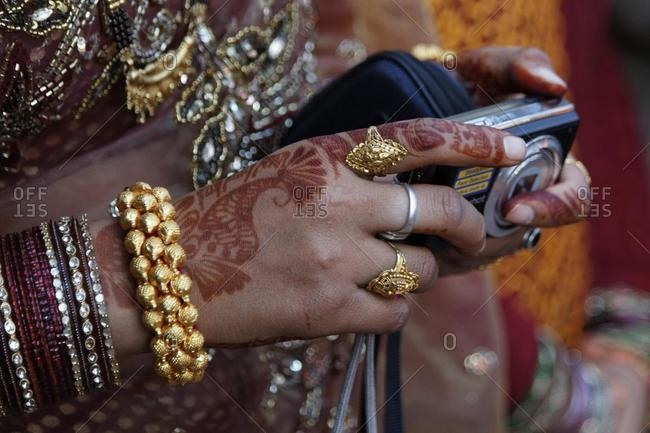 Indian woman\'s decorated hand holding a digital camera, Golu Devta Temple or Golu Devata Temple, Temple of the Bells, a temple for the God Golu, Ghorakhal, Uttarakhand, North India, India, Asia