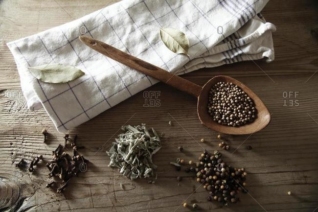 Coriander (Coriandrum sativum), Peppercorns (Piper nigrum), Sage (Salvia) and dried Cloves (Syzygium aromaticum) with a wooden spoon and a kitchen towel on a rustic wooden surface