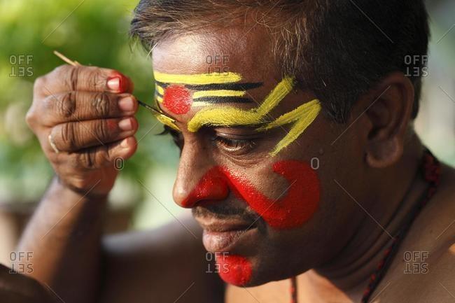 Kathakali dancer doing his make up, Chuvanna Thaadi mask, Kerala, southern India, Asia