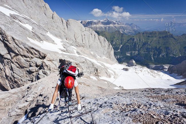 Westgrat fixed rope route, climber ascending to the Marmolada, behind the Sella and the Heiligkreuzkofel group and Fedaia pass, Dolomites, South Tyrol, Italy, Europe