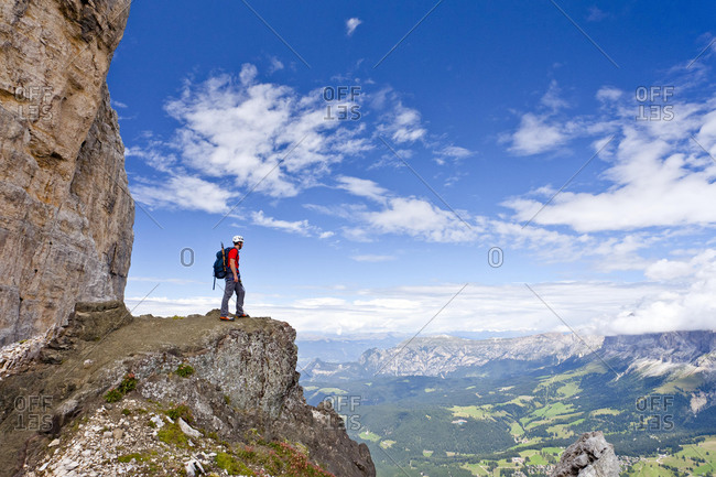 Climber crossing the Latemar mountains, fixed rope route, Dolomites, behind the Rosengarten group, South Tyrol, Italy, Europe