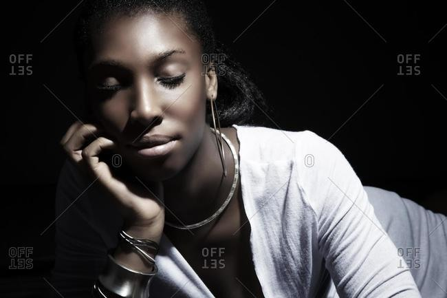Young dark-skinned woman with eyes closed, resting her chin on her hand dreamily
